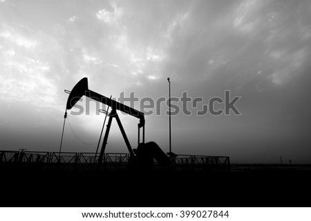 Cloudy sunset and silhouette of crude oil pump in the oil field - Black and white
