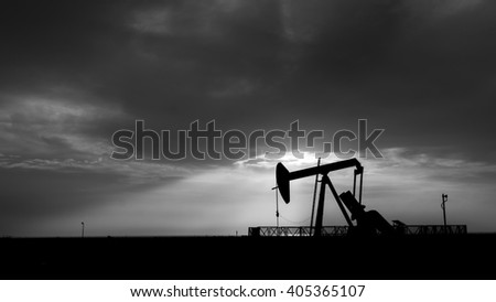 Cloudy Sunset and silhouette of crude oil pump unit in oilfield- black and white