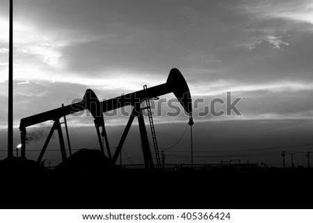 Cloudy Sunset and silhouette of crude oil pump units in oilfield- Black and white