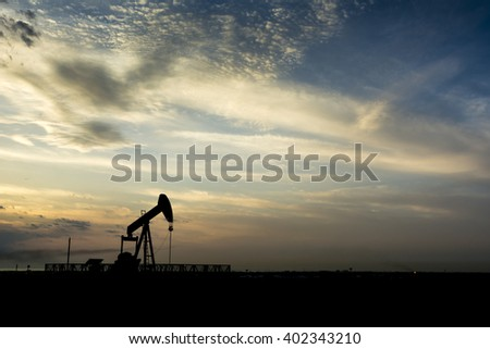 Cloudy sunset and silhouette of crude oil pumping unit in the oil field - Bahrain