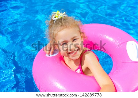 Clouse-up portrait of funny little girl swims in a pool in an pink life preserver - stock photo
