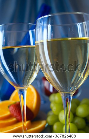 Clouseup of glasses of white wine with oranges and grapes - stock photo