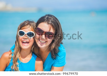 Clouseup portrait of mother and her daughter having fun on tropical beach - stock photo