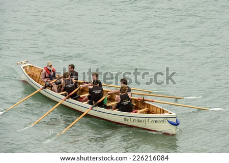 CLOVELLY, UNITED KINGDOM - AUGUST 16 a rowing boat  makes its way to competition ground during the Copilot Gigs Regatta rowing competition, shot on 2014 august 16, Clovelly, Devon, United Kingdom  - stock photo