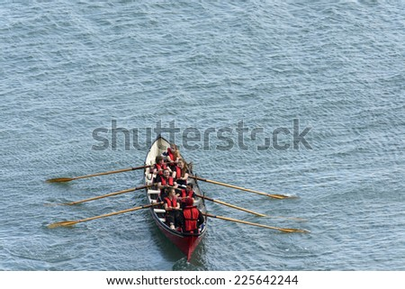 CLOVELLY, UNITED KINGDOM - AUGUST 16 a rowing boat with female team makes its way to competition ground during the Copilot Gigs Regatta , shot on 2014 august 16, Clovelly, Devon, United Kingdom  - stock photo
