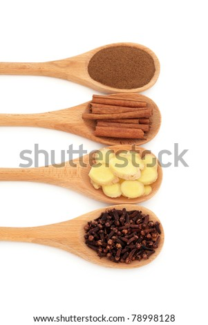 Cloves, fresh ginger, cinnamon sticks and ground allspice in wooden spoons isolated over white background.