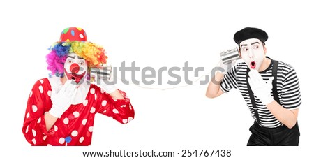 Clown and a mime artist talking through a tin can phone isolated on white background   - stock photo