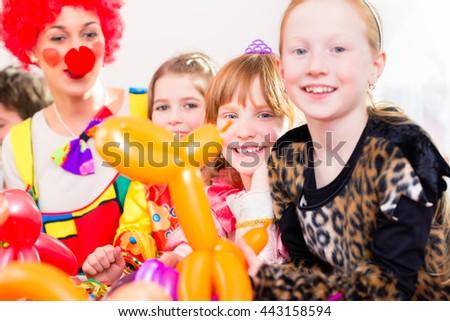 Clown at children birthday party entertaining the kids - stock photo