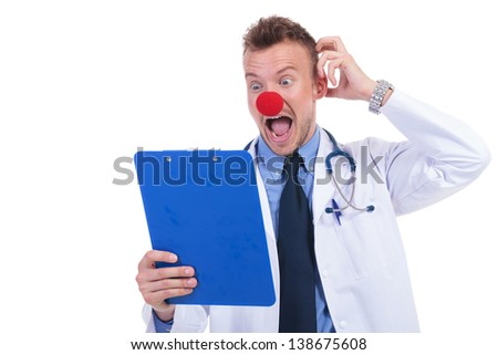clown doctor unable to read the notes on his notepad and looking foolish - stock photo