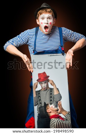 Clown grimacing with mirror two clowns  - stock photo
