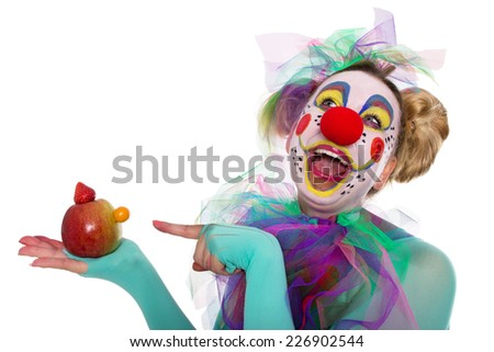 Clown laughs about the small nose of a fruit manikin - stock photo