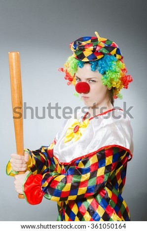 Clown with baseball bat in funny concept