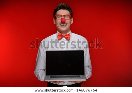 Clown with laptop. Cheerful man with clown holding a laptop while standing isolated on red - stock photo