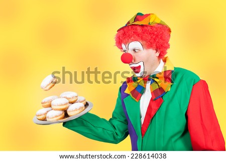 clown with pancake on tray on yellow background - stock photo