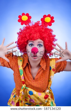 Clown woman on blue background studio shooting. Professional lighting