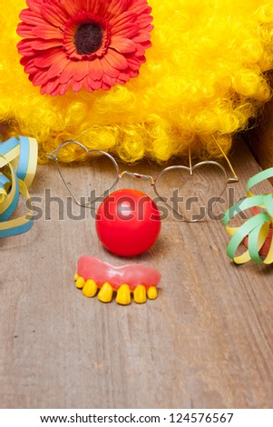 Clowns costume with rotten teeth laying on a wooden board