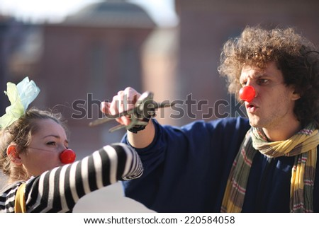 Clowns playing with toy airplane; street pantomime - stock photo