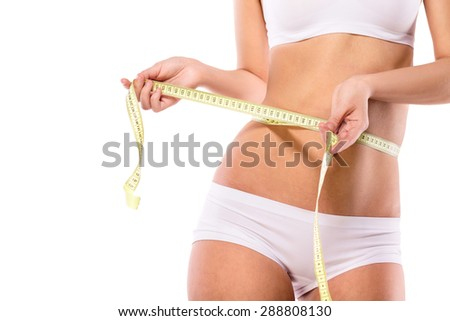 Clsoe up of young slim fit girl with sporty figure measuring her waist with soft meter isolated on a white backdrop