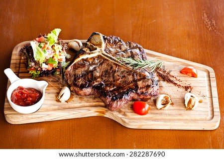 Club Beef steak with pepper sauce and Grilled vegetables on cutting board on dark wooden background - stock photo
