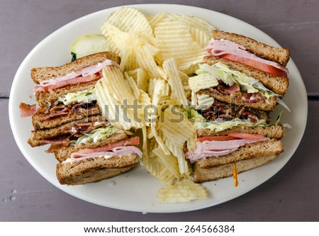 Club sandwich with bacon, turkey, lettuce, tomato and mayonnaise on wheat bread with potato chips photographed from directly above.  - stock photo