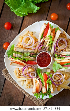 Club sandwich with cheese, cucumber, tomato, smoked meat and salami. Served with French fries. Top view - stock photo