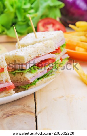 Club Sandwich with Cheese, Pickled Cucumber, Tomato and ham. Garnished with French Fries