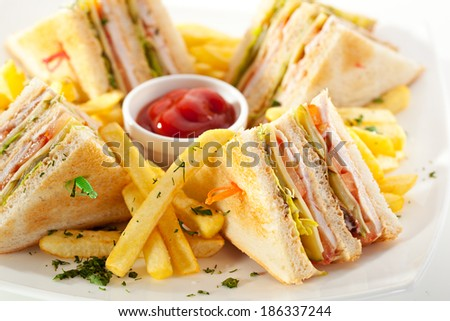 Club Sandwich with Cheese, Pickled Cucumber, Tomato and Smoked Meat. Garnished with French Fries - stock photo