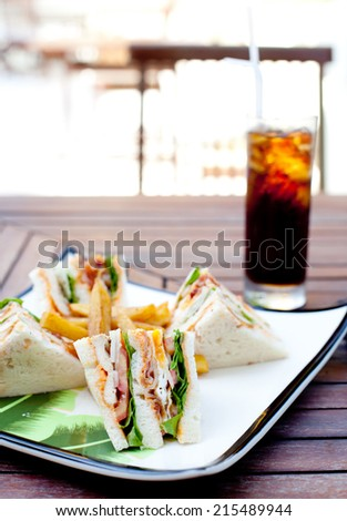 Club sandwich with iced soda drink on a wooden table. Fast food.