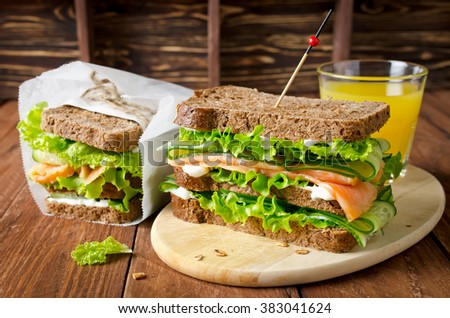 Club sandwich with salmon and cucumbers on dark rye bread - stock photo