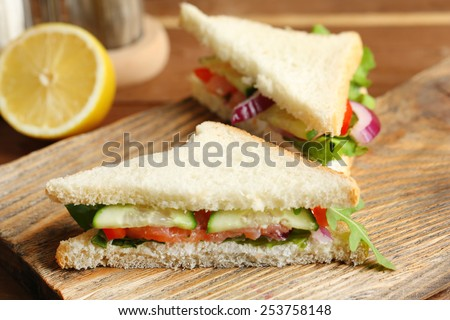 Club sandwich with salmon on wooden background - stock photo