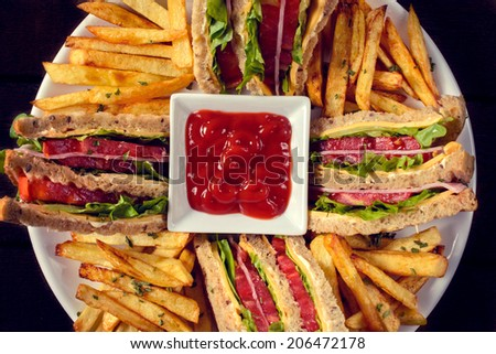 Club sandwiches and french fries in the plate from above