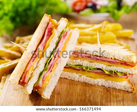 club sandwiches with french fries on wooden table - stock photo