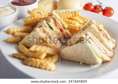 Club sandwiches with grilled chicken, tomato, lettuce, cheese, cucumber and dressing sauce, served on a white plate with french fries.