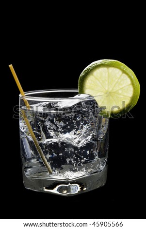 Club soda or Gin or Vodka and tonic with lime slice garnish on a black background