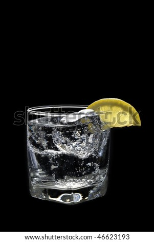 Club soda or Vodka / Gin and tonic mixed drink with lemon slice on a black  background