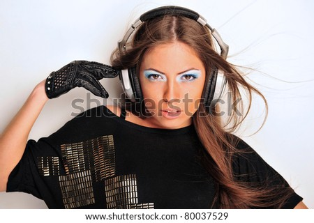 Club style woman with headphones listening to music looking at camera