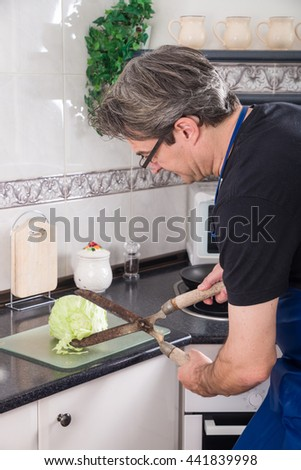 Clueless guy chopping lettuce with a hedge clipper