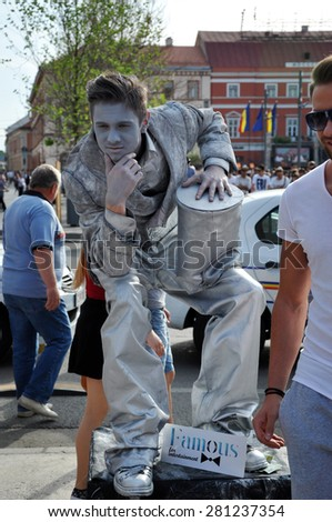 CLUJ NAPOCA - MAY 24: Living statue performer in a silver costume doing a busking mime, inside the Man.In.Fest during the Cluj Days of Cluj. On May 24, 2015 in Cluj, Romania