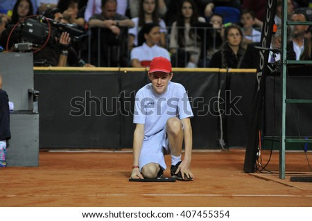 CLUJ-NAPOCA, ROMANIA - APRIL 16, 2016:  Ball boy, caddy in action during a Fed Cup tennis match, Romania against Germany - stock photo