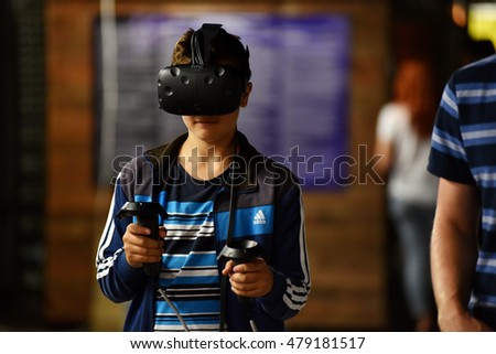 CLUJ-NAPOCA, ROMANIA - AUGUST 5, 2016: Boy tries virtual reality HTC Vive headset and hand controls during the virtual reality exposition, at the Untold Festival