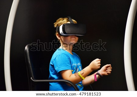CLUJ-NAPOCA, ROMANIA - AUGUST 5, 2016: Boy tries virtual reality Samsung Gear VR headset and hand controls during the virtual reality exposition, at the Untold Festival