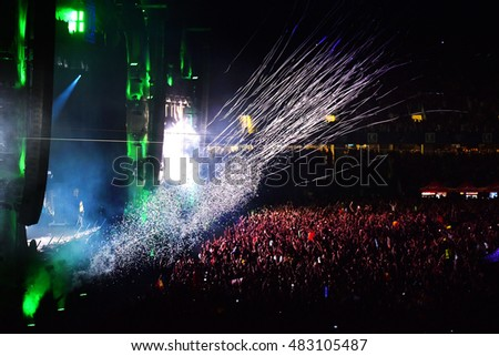 CLUJ NAPOCA, ROMANIA - AUGUST 7, 2016: Crowd of people partying during a live W&W concert. Throwing confetti from the stage at Untold festival