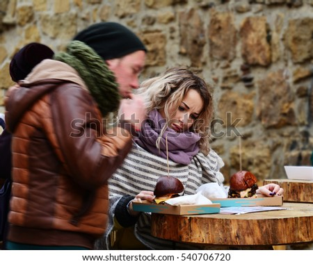 CLUJ-NAPOCA, ROMANIA - DECEMBER 17, 2016: Beautiful young woman tries to choose one of two burgers at a street food table with an undecided face expression