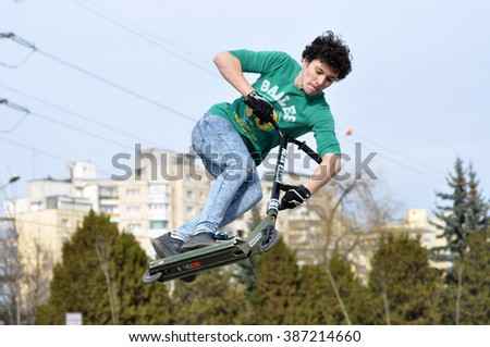 CLUJ-NAPOCA, ROMANIA - FEBRUARY 28, 2016: Young guy doing jumping tricks with his scooter in the Skate Park of Cluj - stock photo