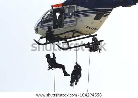 CLUJ-NAPOCA, ROMANIA - MAY.05 : Men climb down from Police helicopter at Eighty Years from inauguration of airport anniversary Air Show, on a mission demonstration May 05,2012 at airport in Cluj ,RO - stock photo