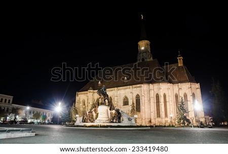 CLUJ-NAPOCA, ROMANIA - 9 NOVEMBER 2014: Unirii Square in Cluj Napoca Trnasylvania Region of Romania with St. Michael Church and Matei Corvin Statue during night time - stock photo