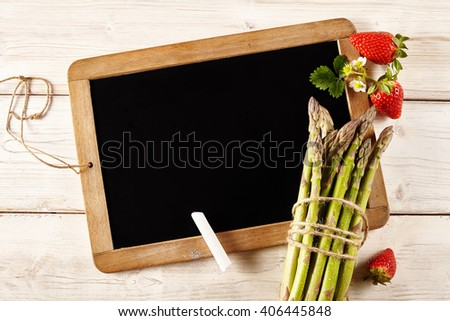 Cluster of ripe red strawberries with green asparagus on an old school slate with copy space for your menu or marketing on rustic wooden boards, overhead view - stock photo