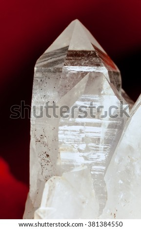 Cluster of rock crystals or pure quartz, a clear macrocrystalline variety of silica (SiO2) on red background. This gemstone is said to have strong healing power. Birthstone for April - stock photo