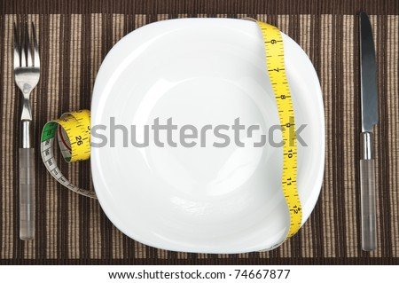 Cm ruler on plate with fork and knife