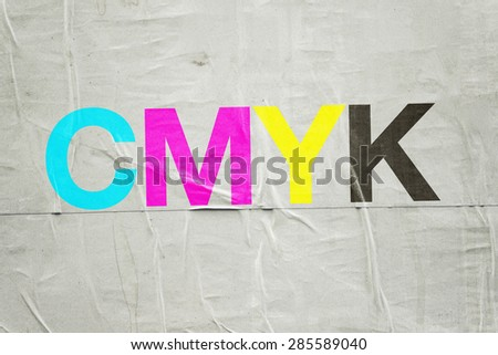 CMYK Digital Printing Technology with Cyan, Magenta, Yellow and Black Letters on Glued Poster Paper - stock photo